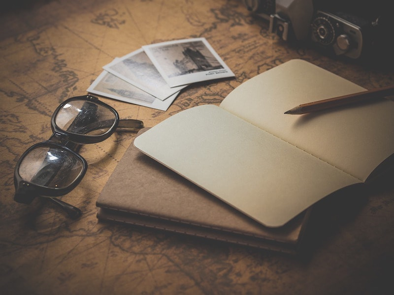 Vintage glasses and photos with an open blank notebook