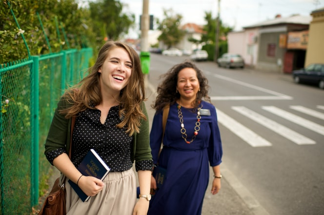 two female missionaries on a sidewalk, smiling