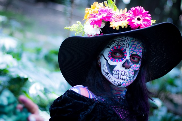 person in day of the dead makeup and flowery hat